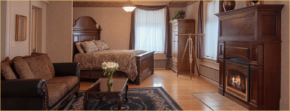 A Bedroom boasts a warm fireplace, large windows, a telescope, and wood accents.