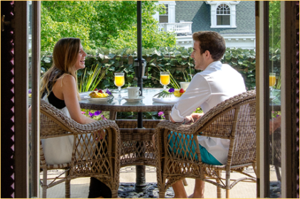 A couple enjoying a gourmet breakfast outside on the terrace