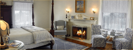 A bedroom boasts a luxurious bed, a small dining area, and a roaring fireplace