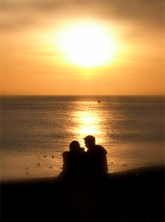 A couple sits on the beach to watch the sunset