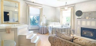 A beautiful room boasting a plush bed, fireplace, in suite jacuzzi, fireplace, and large windows.